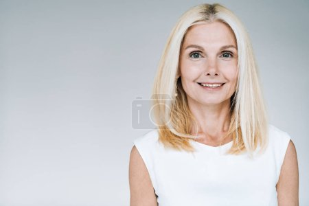 Photo for Happy blonde mature woman smiling isolated on grey - Royalty Free Image