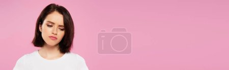 panoramic shot of beautiful sad girl isolated on pink
