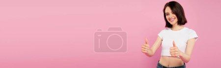 Photo pour Plan panoramique de belle fille souriante montrant pouces vers le haut isolé sur rose - image libre de droit
