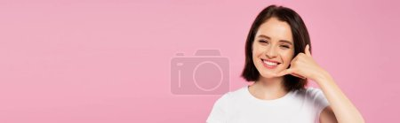Photo pour Tir panoramique de belle fille de sourire affichant m'appeler geste isolé sur le rose - image libre de droit