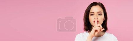 Photo pour Plan panoramique de belle fille montrant signe de silence isolé sur rose - image libre de droit