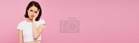 Photo pour Plan panoramique de belle fille triste avec mal de dents isolé sur rose - image libre de droit