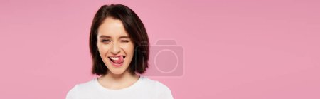 Photo pour Tir panoramique de la belle fille affichant la langue et le clin d'oeil d'isolement sur le rose - image libre de droit