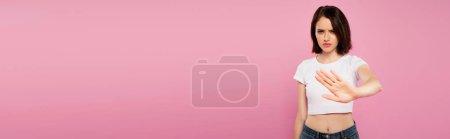 Foto de Plano panorámico de hermosa chica seria mostrando gesto de stop aislado en rosa - Imagen libre de derechos