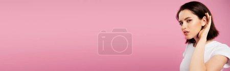 Photo pour Tir panoramique de belle fille focalisée écoutant d'isolement sur le rose - image libre de droit