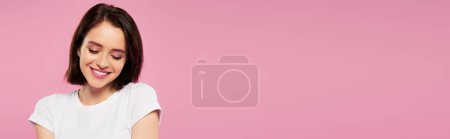 Photo for Panoramic shot of beautiful smiling shy girl looking down isolated on pink - Royalty Free Image