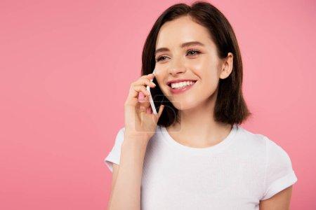 Photo pour Belle fille souriante parlant sur smartphone isolé sur rose - image libre de droit