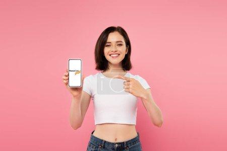 Photo pour Kiev, Ukraine - 3 juillet 2019: fille souriante pointant du doigt sur le smartphone avec le logo du club Forex isolé sur le rose - image libre de droit