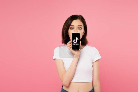 Photo pour Kiev, Ukraine - 3 juillet 2019: fille choquée tenant smartphone avec le logo de tiktok d'isolement sur le rose - image libre de droit