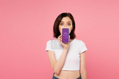 Photo pour Kiev, Ukraine - 3 juillet 2019: fille choquée tenant smartphone avec le logo instagram isolé sur le rose - image libre de droit