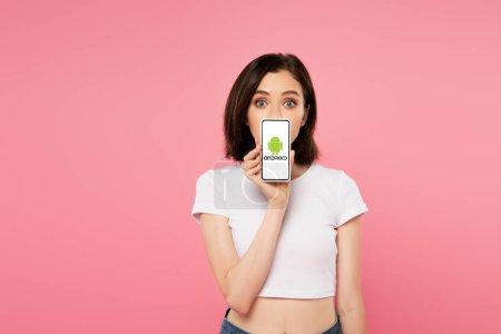 Photo pour Kiev, Ukraine - 3 juillet 2019: smartphone choqué tenant avec logo android isolé sur le rose - image libre de droit