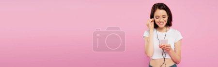 Photo pour Plan panoramique de fille souriante écoutant de la musique dans les écouteurs avec smartphone isolé sur rose - image libre de droit