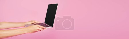cropped view of girl holding laptop with blank screen isolated on pink