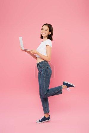 Photo pour Pleine longueur vue de sourire jolie fille posant avec ordinateur portable isolé sur rose - image libre de droit