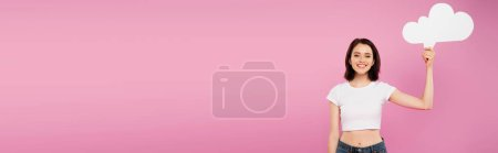Photo for Panoramic shot of smiling pretty girl holding blank white thought bubble isolated on pink - Royalty Free Image