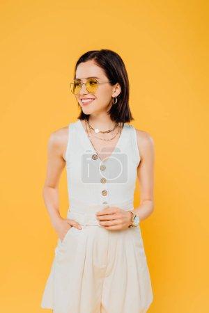 Photo pour Élégante femme aux lunettes de soleil souriant isolé sur jaune - image libre de droit
