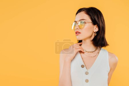 Photo for Elegant woman in sunglasses posing isolated on yellow - Royalty Free Image
