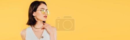 Foto de Foto panorámica de mujer elegante en gafas de sol posando aislado en amarillo - Imagen libre de derechos
