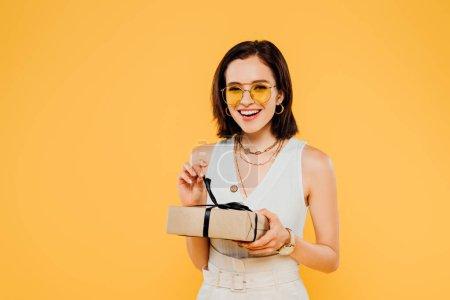 Photo pour Excité souriant femme élégante dans des lunettes de soleil tenant boîte cadeau isolé sur jaune - image libre de droit