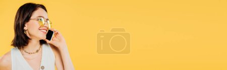Photo for Panoramic shot of  smiling elegant woman in sunglasses talking on smartphone isolated on yellow - Royalty Free Image