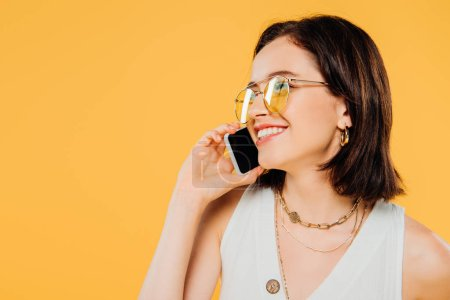 Photo for Smiling elegant woman in sunglasses talking on smartphone isolated on yellow - Royalty Free Image