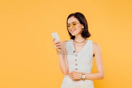Photo pour Femme élégante de sourire dans des lunettes de soleil utilisant le smartphone d'isolement sur le jaune - image libre de droit
