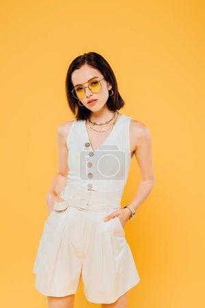 Photo pour Femme élégante dans des lunettes de soleil posant avec les mains dans des poches isolées sur jaune - image libre de droit