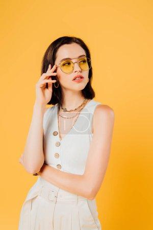 Photo pour Femme élégante dans des lunettes de soleil regardant loin isolé sur le jaune - image libre de droit