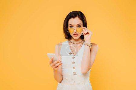 Foto de Mujer sorprendida en gafas de sol sosteniendo teléfono inteligente y tocando gafas de sol aisladas en amarillo - Imagen libre de derechos