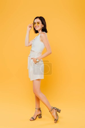 full length view of smiling stylish woman in sunglasses posing with hand in pocket isolated on yellow