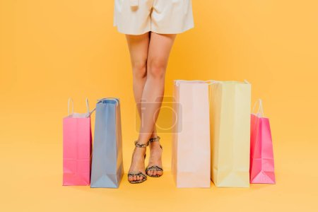 Photo for Cropped view of woman with crossed legs near shopping bags isolated on yellow - Royalty Free Image