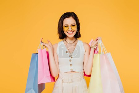 Photo for Smiling woman in sunglasses holding shopping bags isolated on yellow - Royalty Free Image