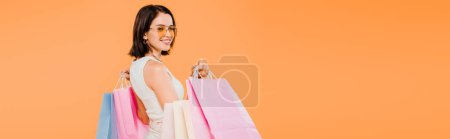 Photo for Panoramic shot of smiling happy woman in sunglasses holding shopping bags isolated on orange - Royalty Free Image