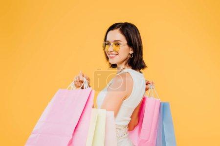 Photo pour Souriant femme heureuse dans des lunettes de soleil tenant des sacs à provisions isolés sur jaune - image libre de droit