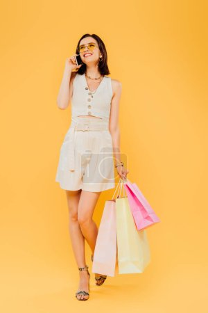 Photo for Full length view of smiling woman in sunglasses holding shopping bags and talking on smartphone isolated on yellow - Royalty Free Image