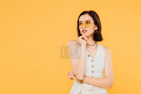 Photo for Dreamy fashionable girl in sunglasses looking away isolated on yellow - Royalty Free Image