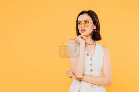 Foto de Chica de moda de ensueño en gafas de sol mirando hacia otro lado aislado en amarillo - Imagen libre de derechos