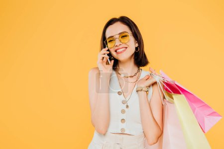 Photo for Happy fashionable girl in sunglasses with shopping bags talking on smartphone isolated on yellow - Royalty Free Image
