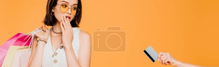 Photo for Shocked fashionable girl in sunglasses with shopping bags looking at credit card isolated on orange - Royalty Free Image