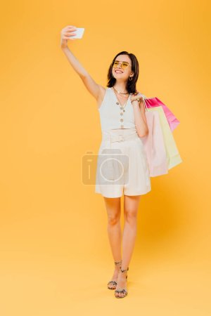 Photo pour Heureuse fille à la mode dans des lunettes de soleil avec des sacs à provisions prendre selfie sur smartphone isolé sur jaune - image libre de droit