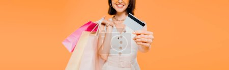 cropped view of happy girl with shopping bags presenting credit card isolated on orange