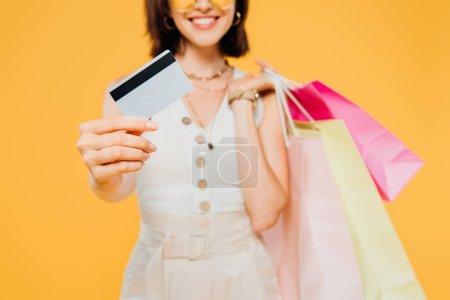 Foto de Vista recortada de chica feliz con bolsas de compras presentando tarjeta de crédito aislada en amarillo - Imagen libre de derechos