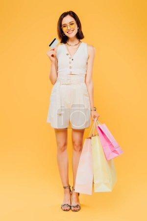 Photo pour Fille heureuse dans des lunettes de soleil avec des sacs à provisions tenant la carte de crédit isolé sur jaune - image libre de droit