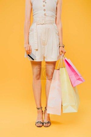 Photo pour Vue recadrée de femme avec des sacs à provisions retenant la carte de crédit d'isolement sur le jaune - image libre de droit