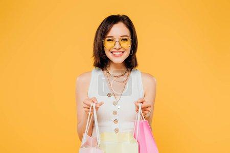 Foto de Chica feliz de moda en gafas de sol sosteniendo bolsas de compras aisladas en amarillo - Imagen libre de derechos