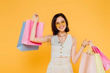 Photo pour Fille à la mode de sourire dans des lunettes de soleil retenant des sacs à provisions d'isolement sur le jaune - image libre de droit