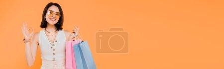 Photo pour Fille à la mode heureuse dans des sacs à provisions de fixation de lunettes de soleil et affichant le signe correct d'isolement sur l'orange - image libre de droit