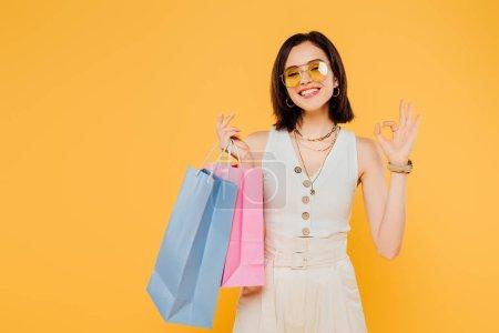 Photo pour Heureux fille à la mode dans des lunettes de soleil tenant des sacs à provisions et montrant OK signe isolé sur jaune - image libre de droit
