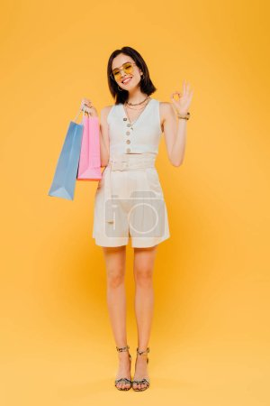 smiling girl in sunglasses holding shopping bags and showing okay sign isolated on yellow