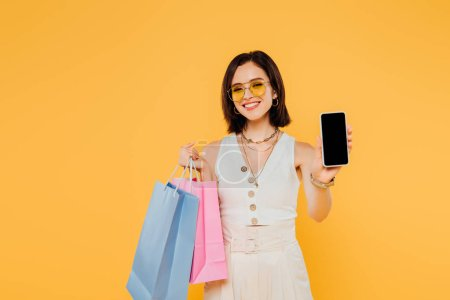Photo pour Fille à la mode heureuse dans des lunettes de soleil avec des sacs à provisions affichant le smartphone avec l'écran blanc isolé sur le jaune - image libre de droit